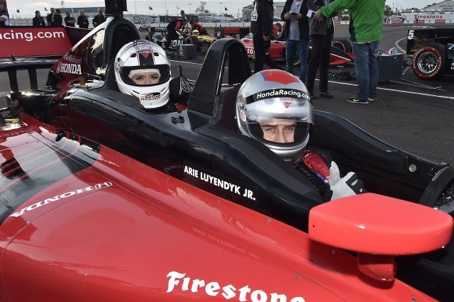 Arie Luyendyk Jr. and Lauren Burnham ride in a Hondy Indycar race car