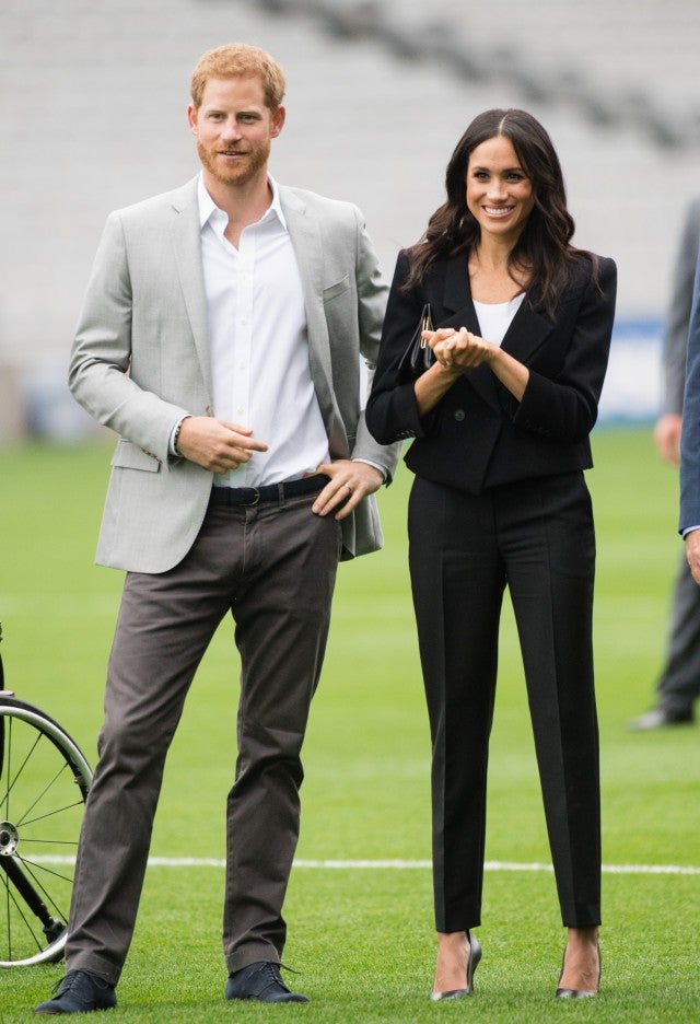 Meghan Markle in black pantsuit with Prince Harry on soccer field