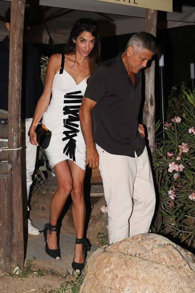 Amal Clooney in black and white dress with George Clooney