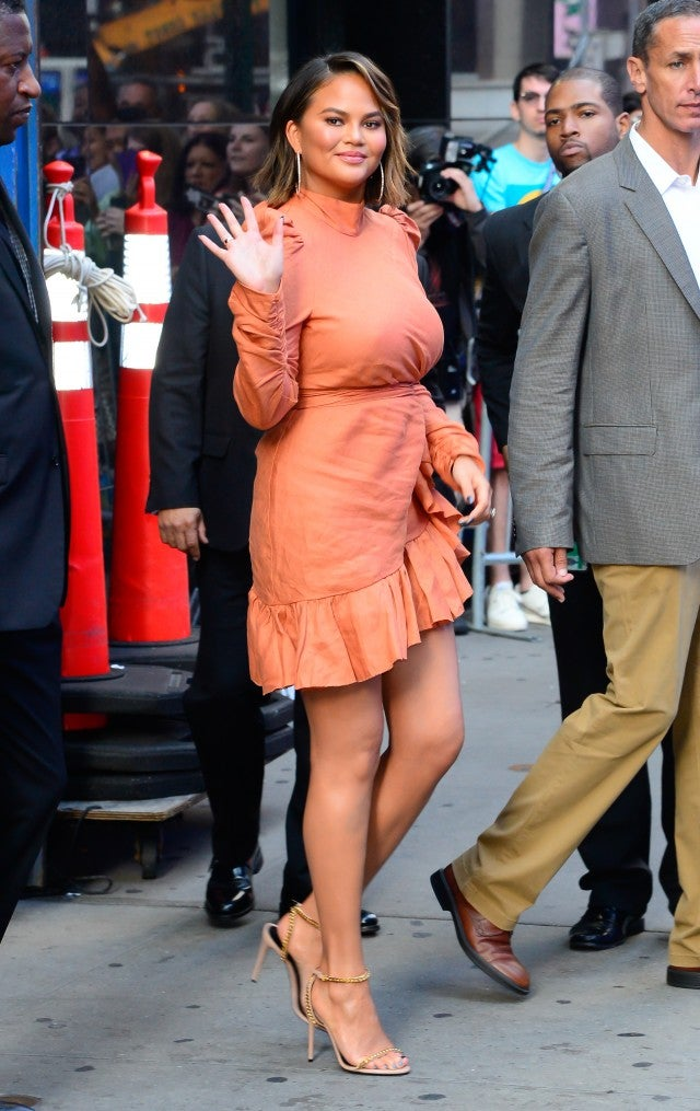 Chrissy Teigen in orange dress