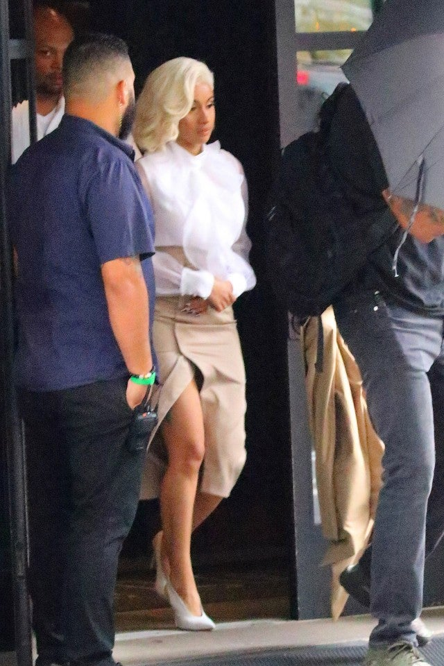 Cardi B looks stylish, in a thigh-high slit skirt and white blouse, as she leaves her hotel on her way to turn herself in to police in New York City, NY, in connection to a fight at a Queens strip club.