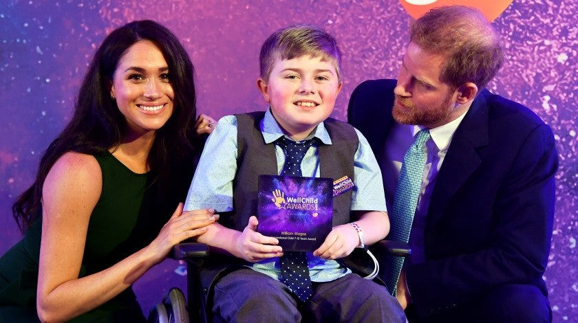 Prince Harry and Meghan Markle pose for a photo with award winner William Magee during the WellChild Awards