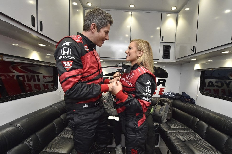 Arie Luyendyk Jr. and Lauren Burnham wear Honda racecar uniforms