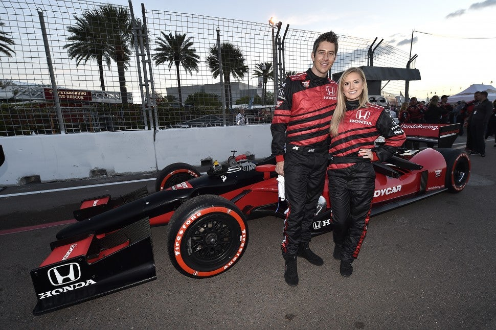 Arie Luyendyk Jr. and Lauren Burnham pose with Honda race car