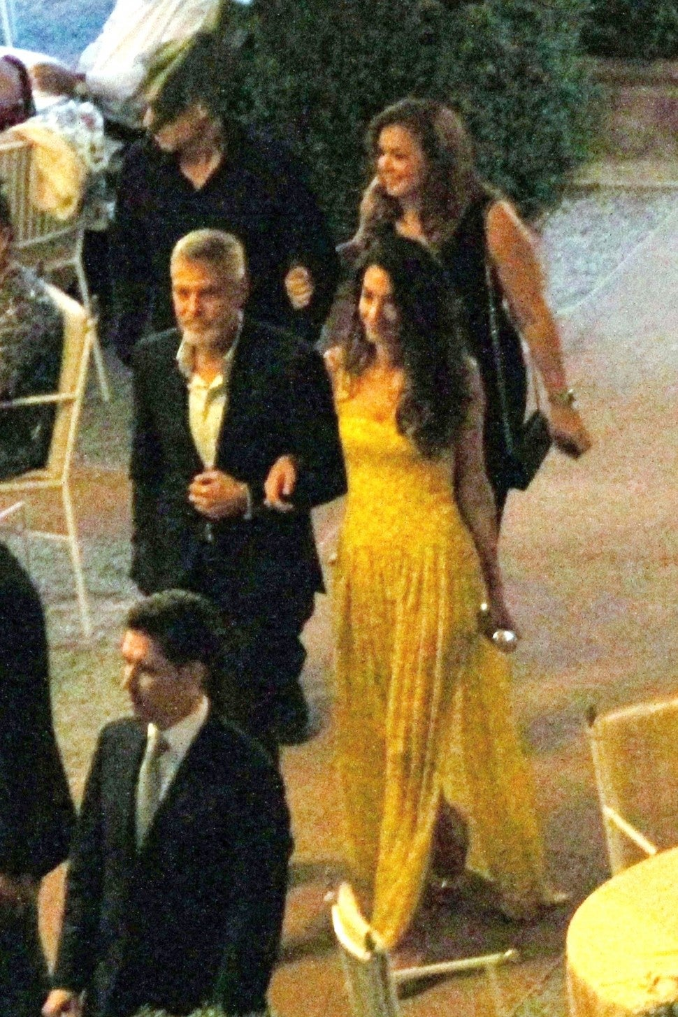Amal Clooney in yellow dress with George Clooney