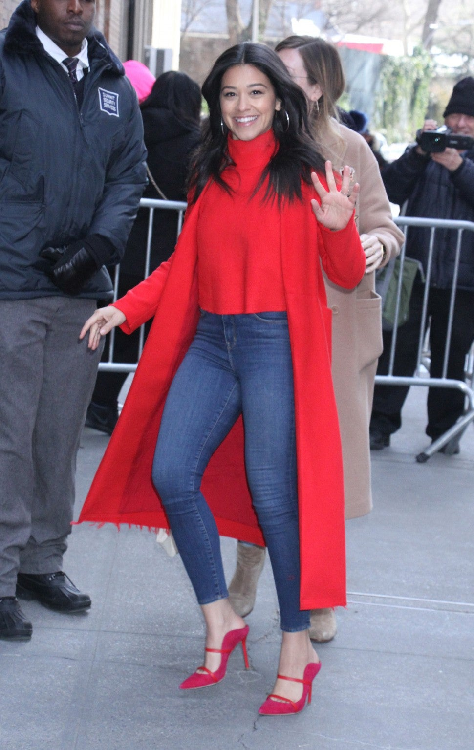 Gina Rodriguez in skinny jeans and red coat