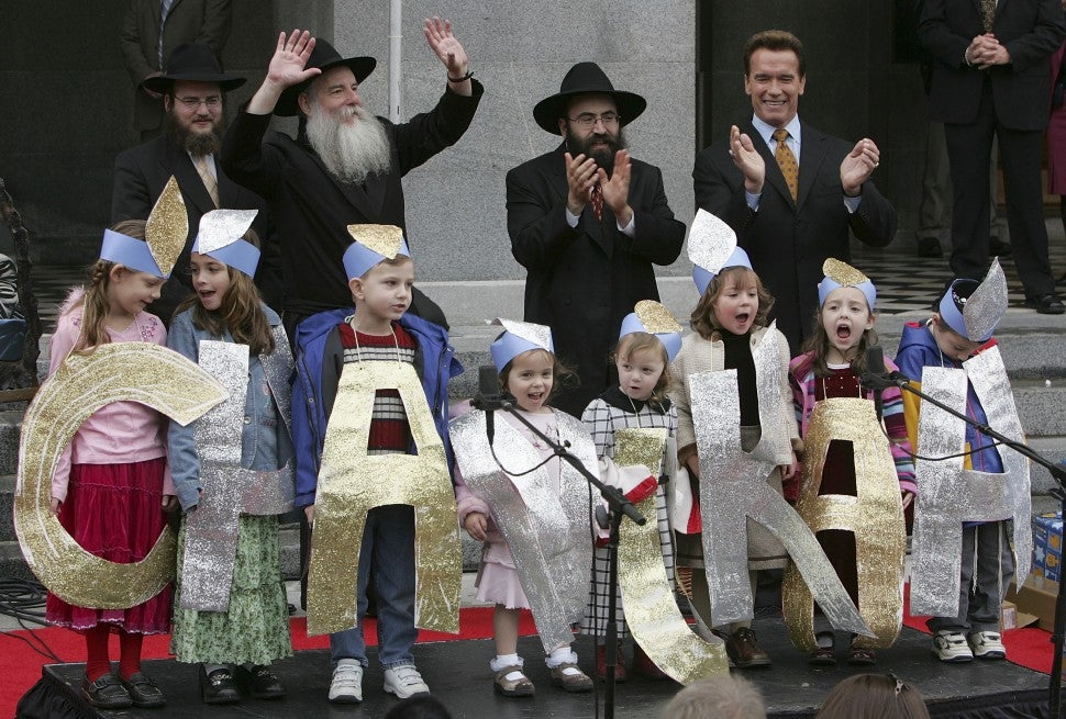 Arnold Schwarzenegger (R) claps as the Chabad Tiny Tots Children's Choir sings during 12th annual Chanukah celebration