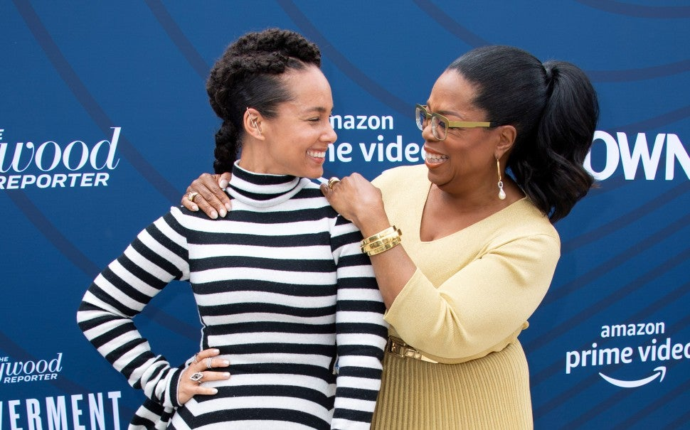 Alicia Keys (L) and US media executive, actress and talk show host Oprah Winfrey laugh as they attend The Hollywood Reporter's Empowerment In Entertainment Event