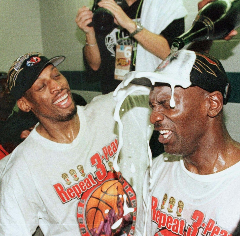 Dennis Rodman (L) of the Chicago Bulls pours champagne on the head of teammate Michael Jordan (R) 14 June after winning game six of the NBA Finals with the Utah Jazz at the Delta Center in Salt Lake City, UT.