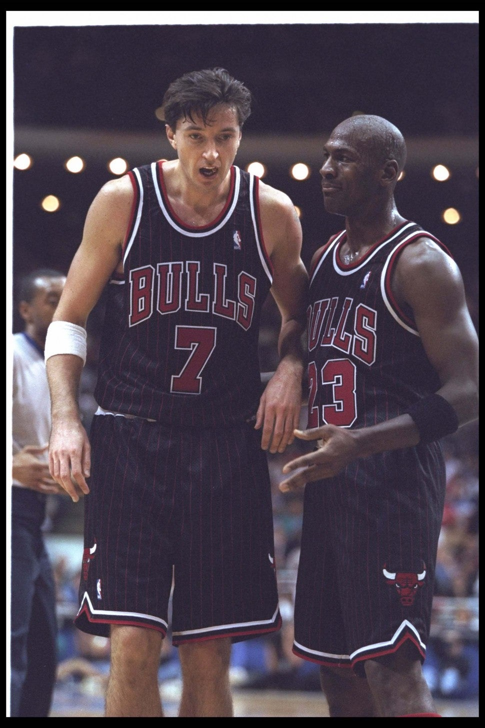 Toni Kukoc (left) and guard Michael Jordan confer during a game against the Orlando Magic at the Orlando Arena in Orlando, Florida.