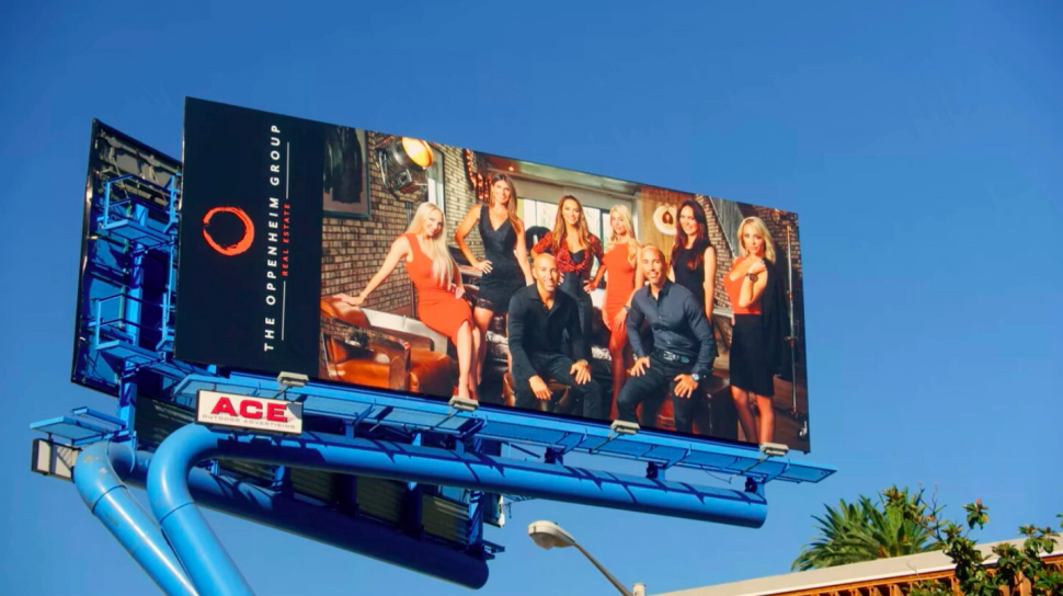 The cast of 'Selling Sunset' on a billboard for The Oppenheim Group.