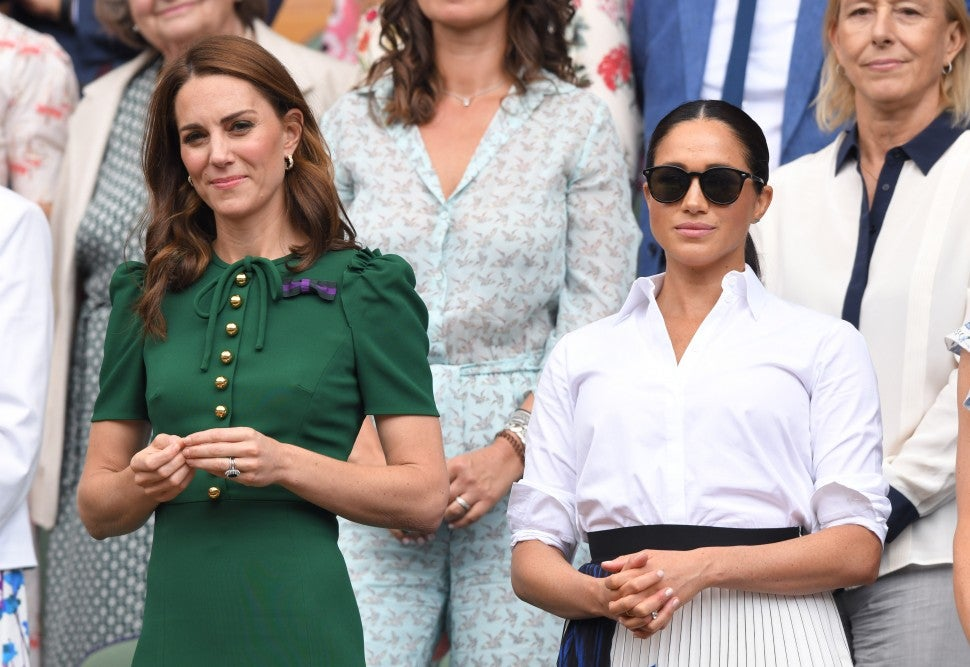 Catherine, Duchess of Cambridge and Meghan, Duchess of Sussex in the Royal Box on Centre Court during day twelve of the Wimbledon Tennis Championships at All England Lawn Tennis and Croquet Club on July 13, 2019 in London, England.