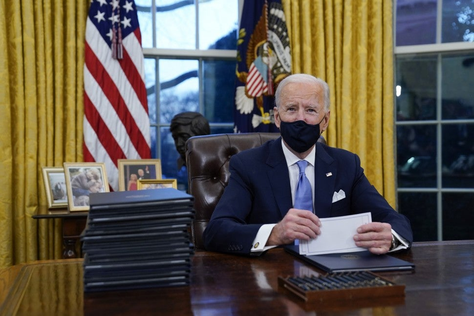 President Joe Biden pauses as he signs his first executive orders in the Oval Office of the White House on Wednesday, Jan. 20, 2021.