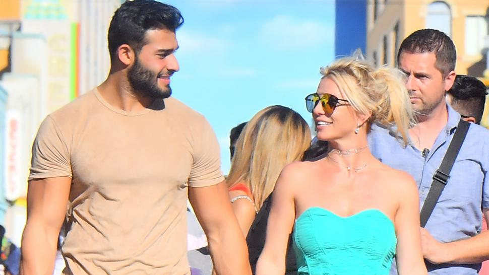 Britney Spears and her boyfriend Sam Asghari hold hands while out celebrating her sons' birthdays at Disneyland