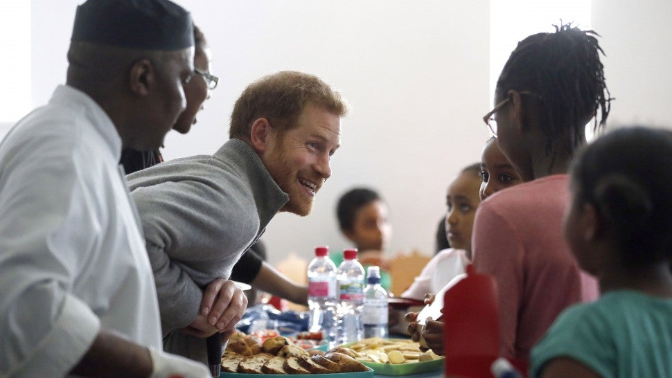 Prince Harry serves food to children as part of the Fit and Fed initiative in London
