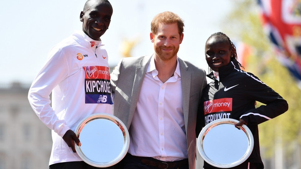 Prince Harry poses with Eliud Kipchoge of Kenya and Vivian Cheruiyot of Kenya as they receive their trophies, following their first place results during the Virgin Money London Marathon at United Kingdom on April 22, 2018 in London, England.