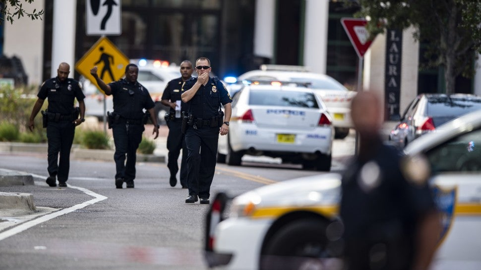 Police gather after an active shooter was reported at the Jacksonville Landing in Jacksonville, Fla., Sunday, Aug. 26, 2018. A gunman opened fire Sunday during an online video game tournament that was being livestreamed from a Florida mall, killing multiple people and sending many others to hospitals.