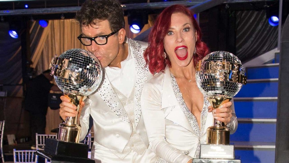Bobby Bones and Sharna Burgess holding their mirror ball trophies after they were announced the winner of DWTS season 27