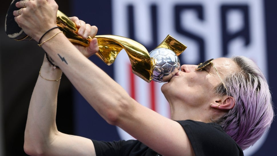 Megan Rapinoe kisses trophy at parade