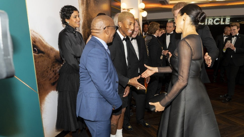 "Prince Harry, Duke of Sussex and Meghan, Duchess of Sussex greet US singer Pharrell Williams at the European Premiere of Disney's ""The Lion King"" at Odeon Luxe Leicester Square on July 14, 2019 in London, England."