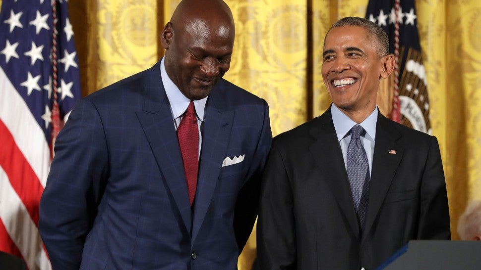 U.S. President Barack Obama smiles up at National Basketball Association Hall of Fame member and legendary athlete Michael Jordan before awarding him with the Presidential Medal of Freedom