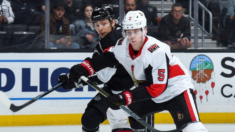 Trevor Moore #12 of the Los Angeles Kings and Mike Reilly #5 of the Ottawa Senators battle for position during the third period at STAPLES Center