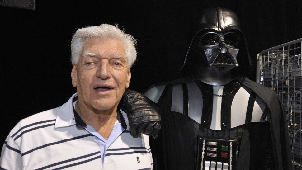 English actor David Prowse (L), who played the character of Darth Vader (Dark Vador in French) in the first Star Wars trilogy poses with a fan dressed up in a Darth Vader costume during a Star Wars convention on April 27, 2013 in Cusset.